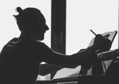 Kompozytor Jan Stokłosa siedzi przy fortepianie i pisze ołówkiem na noutach